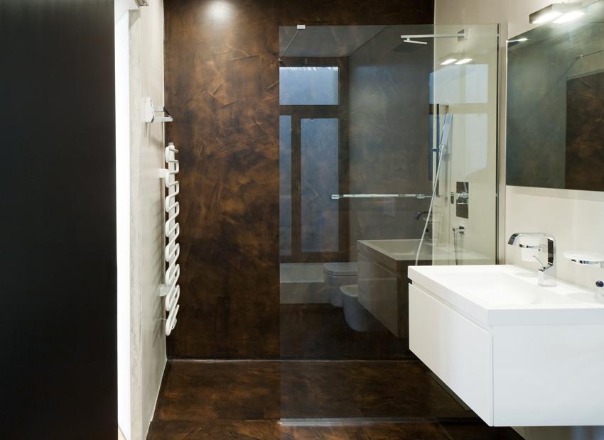 bagno ristrutturato con l'impiego della stessa resina spatolata per pareti e pavimento effetto ossidato