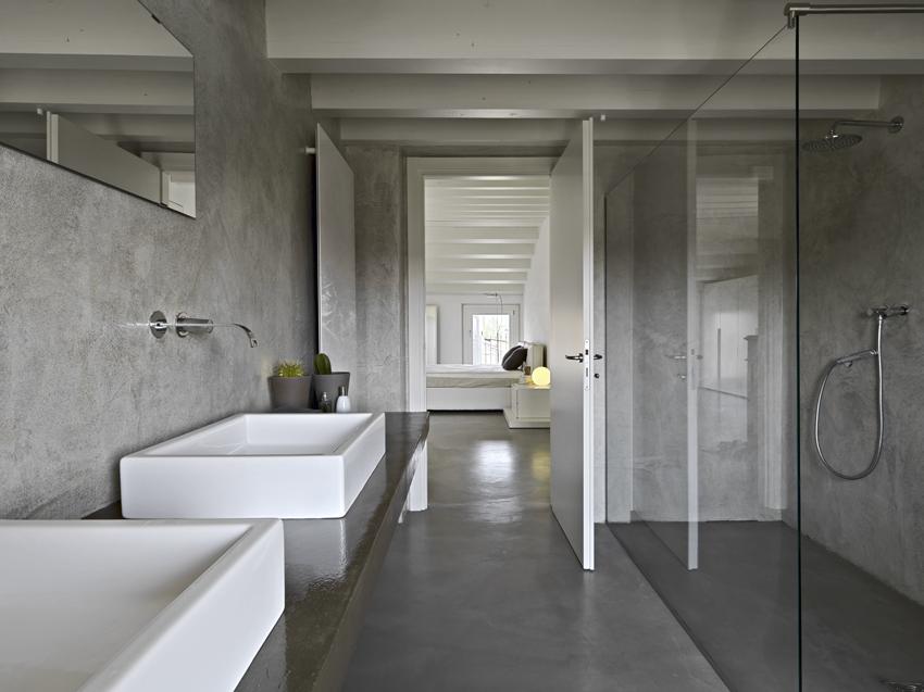 Pareti in resina opaca e pavimento in resina lucida per questo bagno dalle tonalità del grigio