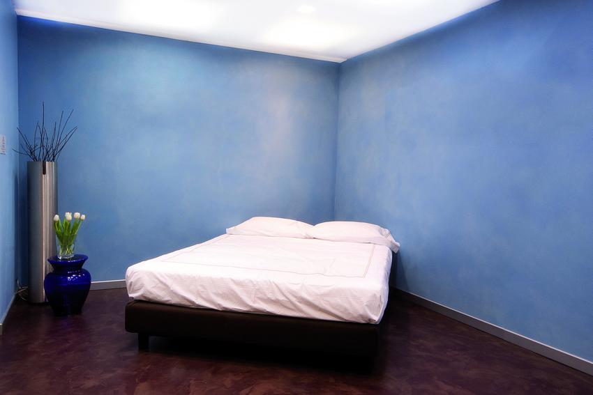 Paresti in resina spatolata azzurra che contrastano con pavimento sempre in resina scura
